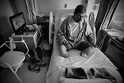Carlos Raposa, 49, sits up on his hospital bed waiting for the nurses to bring him to the dyalisis machine  at Saint Annes hospital in Fall River where he has been for the last 5 days after becoming weak.  Carlos has lost both of his lower legs because of diabetes and struggles to deal with the commitment of getting dyalisis for over 2 hours 3 times a week.  As his condition has worstened over the years Carlos has had greater difficulty dealing with his condition.  Increasingly, Carlos has fallen greater into depression and has turned to smoking and drinking to deal with it.  What used to be monthly visits to the hospital has turned into weekly excursions with ever longer stays in hospital.  Family members have become ever more worried about Carlos' drop in weight and his inability to move on his own any longer.  For someone who was an athletic figure, Carlos has become a shadow of his former self.