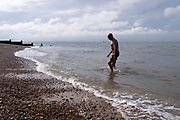 A cold and tired wild swimmer walks over beach shingle after a swim in the cold tidal waters of the Thames Estuary, on 25th July 2021, in Whitstable, England.