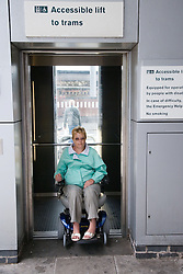 Woman wheelchair user exiting accessible lift to tram stop,