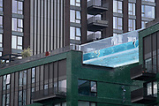 Swimmers enjoy the waters of the Sky Pool, a 25 metres-long transparent water pool bridging two 10-storey residential towers 35 metres above the ground, the largest freestanding acrylic pool structure in the world at EcoWorld Ballymore's new Embassy Gardens development in Nine Elms, on 3rd June 2021, in London, England.