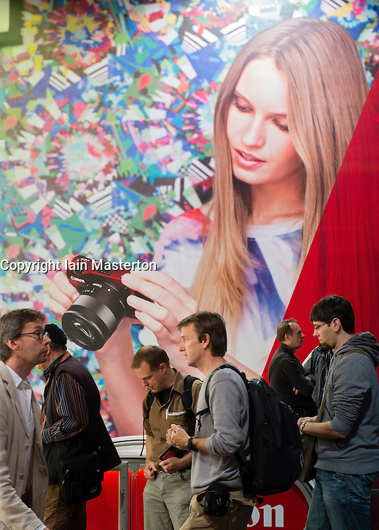 Visitors walk past large poster on second day of bi-annual Photokina photography and imaging trade fair held in Cologne Germany; Wednesday 19 September 2012