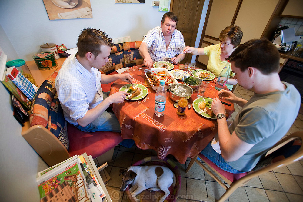 Lunch for Carlo and Marie Paule Kutten-Kass of the town of Erpeldange in Bous, southeast of Luxembourg City, near the German border. Also in the photograph: their sons Joe and Georges. Their daughter was away during the time the photograph was made. Grand Duchy of Luxembourg. The image is part of a collection of images and documentation for Hungry Planet 2, a continuation of work done after publication of the book project Hungry Planet: What the World Eats.