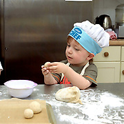 A young boy making bread in the kitchen of Little Green Rascals Children's Organic Day Nursery, nr Elvington, York, North Yorkshire, UK. Little Green Rascals is a children's day nursery that opened in York in July 2009.  It is the first fully organic day nursery in the North of England and has been awarded the Soil Association's Gold Catering Mark for the last four years.