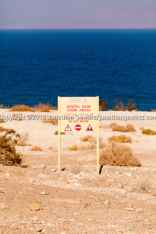 Beach sign warning of sinkhole danger on the Israeli Dead Sea coast near Ein Gedi. WATERMARKS WILL NOT APPEAR ON PRINTS OR LICENSED IMAGES.