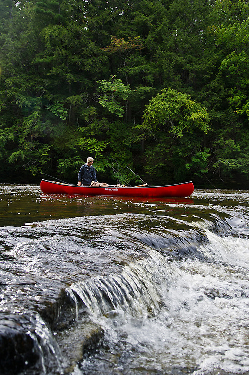 Lining a canoe over rocky ledges between the Upper and Lower Falls of the Tahquamenon River near Newberry Michigan.