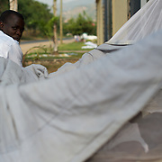 "A burundian university student seeking shelter outside the US embassy in Bujumbura, takes a nap in a improvised tent. The students moved to the area in early May because, they claim, the US authorities ensure their security, after their university was closed amid anti-government protests. The government closed the university at the end of April, citing ""insecurity""."