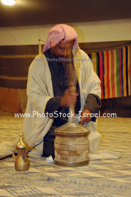 Israel, Negev, Bedouin man preparing coffee in his tent with a manual coffee pounder device