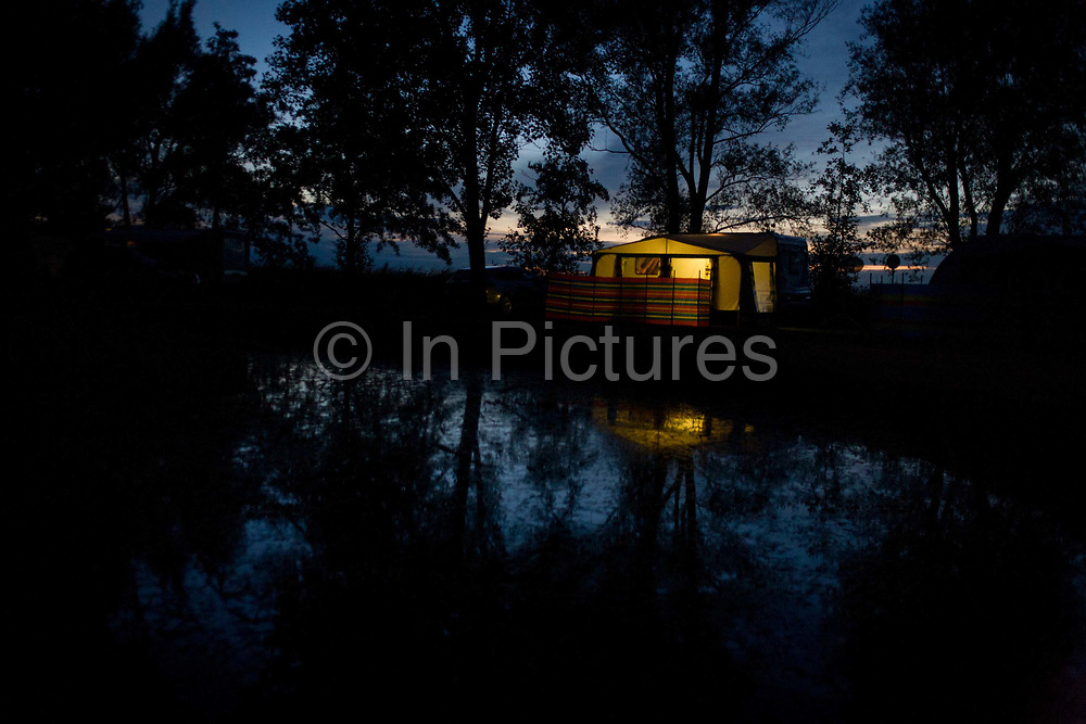 Nightfall on trees and the campsite in Reedham on the Norfolk Broads. A lone caravan with a striped windbreak and a glow from awning lights looks forlorn but peaceful at this tranquil place in front of a duck pond. The last daylight fades behind after another fine summer's day at this popular location in East Anglia know for its flat landscape and wide skies.
