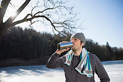 Man drinking water after workout by frozen lake