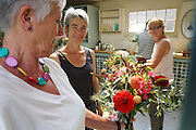 """Rachel running a Sunday morning flower arranging course at 'Green and Gorgeous'. Giving advice and compliments to a participant <br /><br />Rachel is the owner of """"Green and Gorgeous"""" Flower Farm in Oxfordshire. She is well known for the flower arranging courses she offers. Her flower farm also caters for events, weddings and private picking<br /><br />British local flowers, grown nearby, count for around 10% of the UK market, traveling less than a tenth of their foreign counterparts which are often flown in from abroad. Nearly 90% of the flowers sold in the UK are actually imported, and many travel over 3000 miles. Local flower farms help biodiversity, providing food and habitat to a huge variety of wildlife, insects including butterflies, bugs, and bees. Often local flower farmers prefer to grow organic rather than using pesticides. British flowers bloom all the year around, even in the depths of winter, and there are local flower farms throughout the country.<br /><br />Many people like the idea of the just picked from the garden look, and come to flower farms throughout Britain to pick their own for weddings, parties and garden fetes. Others come for the joy of a day out in the countryside with their family. Often a bride and her family will come to pick the flowers for her own wedding, some even plant the seeds earlier in the year."""