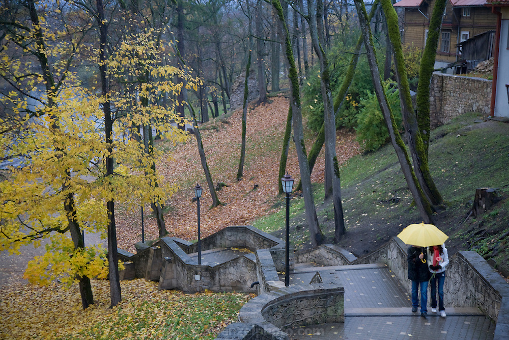 A couple walks in the rain under a yellow umbrella in Cesis, Latvia.