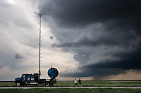 """Storm chasers with Project Vortex 2 watch a distant wall cloud and supercell in Goshen County, Wyoming, June 5, 2009. The truck at right is the """"Doppler on Wheels"""" truck. Project Vortex 2 is a two year National Science Foundation and NOAA funded science mission to study tornadoes and supercell thunderstorms."""