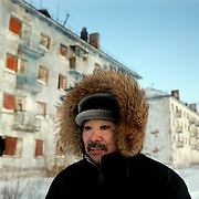 Karp Belgayev, a coal miner, walks through Yor Shor, an abandoned village near Vorkuta where he is among the last ten inhabitants living in empty blocks..Belgayev says the black rings around his eyes are result of not washing properly due to the Arctic cold during ten years working underground..Vorkuta is a coal mining and former Gulag town 1,200 miles north east of Moscow, beyond the Arctic Circle, where temperatures in winter drop to -50C. .Here, whole villages are being slowly deserted and reclaimed by snow, while the financial crisis is squeezing coal mining companies that already struggle to find workers..Moscow says its Far North is a strategic region, targeting huge investment to exploit its oil and gas resources. But there is a paradox: the Far North is actually dying. Every year thousands of people from towns and cities in the Russian Arctic are fleeing south. The system of subsidies that propped up Siberia and the Arctic in the Soviet times has crumbled. Now there's no advantage to living in the Far North - salaries are no higher than in central Russia and prices for goods are higher.