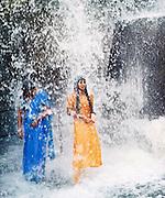 Two girls bathe in the waterfall at Thiruparappu, Kerala, India