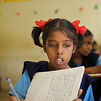 """Vijita in class at the Government Girls High School, Venugopalapuram in Cuddalore.. .Vijita (age 14) and Vijyashree (age 11) Viswanathan lost their mother and brother to the tsunami in 2004. They continue to live in the fishing village of Thazanguda with their father Viswanathan, his second wife Kayalvizhi and their two children Sanjay (age 3) and Monica (age 1). ..Until the beginning of the 2009 academic year in June, Vijita and Vijyashree attended the local Thazanguda school. This village school teaches pupils only until the 8th Standard and with Vijita now entering the 9th, it was decided that the two daughters remain together and both travel 3km to the local town school: the Government Girls High School, Venugopalapuram in Cuddalore. ..At the same time Viswanathan decided he would cease day-to-day care of his daughters and place them in the Government Home for Tsunami Children, also in Cuddalore. This was not a move welcomed by either Vijita or Vijyashree and one afternoon after just two weeks at the orphanage, the two girls ran away. At roll call in the orphanage that evening the alarm was sounded and the two sisters were eventually located in Thazanguda waiting for their father and Kayalvizhi who were both away at the time. Realising his daughters' unhappiness, Viswanathan then took them out of the Government home. ..According to her class teacher, Vijita often compares her step-mother to her mother and concludes that she wants her mother back. Vijita confides in her teachers that her stepmother is forever demanding that she and her sister Vijyashree undertake housework. This frustration at home is tempered by the genuine love both sisters have for their father and two younger siblings Sanjay and Monica. Vijita expresses a lonelyness without her mother. Pushpavalli concludes that """"Vijita wants something else beyond the love of her father and sister"""". ..Viswanathan appears genuinely to want the best for his two elder daughters. His experiment enrolling them at"""