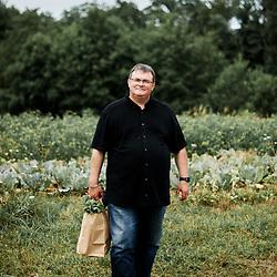 "Franck Bonnet, the mayor of Saint-Fraigne, holding a grocery bag while posing in a vegetable garden, ""le potager de Frugie"". Saint-Pierre-de-Frugie, France. July 12, 2019."