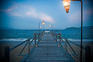 Perspective of a wooden pier leading to a romantic restaurant table with an ocean view. Lanterns and candles reinforce the dreamy feeling. Nha Trang, Vietnam, Asia