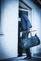 Burglar entering house with a crowbar and bag