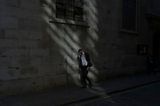City workers within street scene of light and shadow in the City of London, England, United Kingdom.