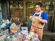 24 FEBRUARY 2016 - BANGKOK, THAILAND: A sidewalk vendor arranges flower garlands she sells in her sidewalk stall in front of a store in Pak Khlong Talat in Bangkok. Bangkok government officials announced this week that vendors in Pak Khlong Talat, Bangkok's well known flower market, don't have to move out on February 28. City officials are trying to clear Bangkok's congested sidewalks and they've cracked down on sidewalk vendors. Several popular sidewalk markets have been closed in recent months and the sidewalk vendors at the flower market had been told they would be evicted at the end of the month but after meeting with vendors and other stake holders city officials relented and said vendors could remain but under stricter guidelines regarding sales hours. The flower market is one of the best known markets in Bangkok and has become a popular tourist destination.        PHOTO BY JACK KURTZ
