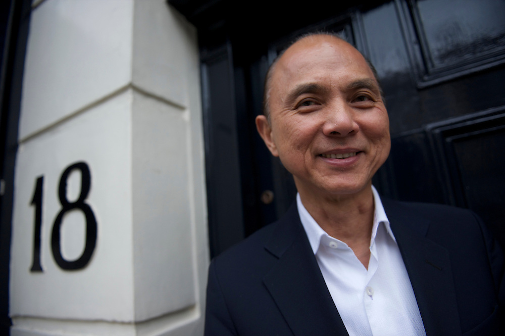 Fashion designer Jimmy Choo poses outside his store on Cannaught Street, London, March 22, 2010.