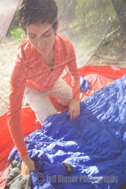 A young woman lays out her sleeping bag at a campsite in southern California.