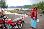 Mo Suo minority woman passes a red motorcycle by Lugu Lake, in Yunnan province. This is genuine traditional dress worn not for tourism, but as everyday dress. This is a poor run down area with little infrastructure such as roads, hotels or things tourists expect. Not for the feint-hearted traveler.