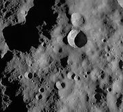 This Dawn framing camera (FC) image of the Asteroid Vesta, shows the Arruntia crater, which is the large crater offset to the top right of the center of the image. Slightly over half of Arruntia crater is covered in a large shadow. But, the non-shadowed part of Arruntia shows impressive details. There is bright material cropping out slightly below the left rim and just below the top and bottom rims there are distinct ridges of material, which are probably formed by material from the rim cascading down towards the center of Arruntia. This image is located in Vesta's Bellicia quadrangle, in Vesta's northern hemisphere. NASA's Dawn spacecraft obtained this image with its framing camera on Oct. 24, 2011.