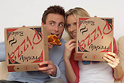 couple on a sofa eating pizza, fast food high in fat and salt, tv dinner<br />
