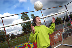 Sports club for homeless teenagers; Leeds, Boy with football; UK