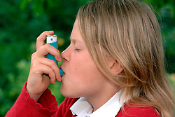 girl using her asthma pump