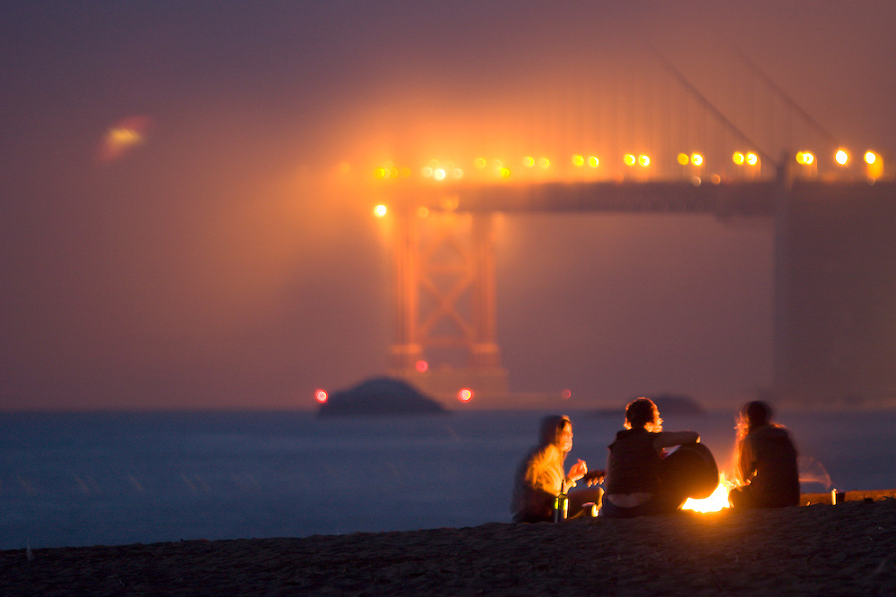 Group of girls hanging out around campfire on Baker Beach playing music at sunset. Presidio of San Francisco. Golden Gate National Recreation Area. San Francisco,  CA