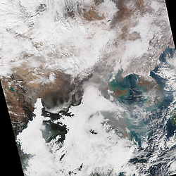 """As world leaders converged on Paris for a United Nations conference on climate change, residents of Beijing and other cities in eastern China faced the most severe air pollution the nation has seen in 2015. Chinese authorities issued an """"orange"""" air pollution alert, the second highest level on a four-tiered warning scale. They advised millions of people to stay indoors, halted construction at some sites, and ordered factories to close, according to news reports.<br /> The Visible Infrared Imaging Radiometer Suite (VIIRS) on the Suomi NPP satellite acquired this natural-color image of northeastern China on November 30, 2015. The image shows extensive haze, low clouds, and fog over the region. The brightest areas are clouds or fog, which have tinges of gray or yellow because of the air pollution. Other cloud-free areas have a pall of gray haze that mostly blots out the cities below. In areas where the ground is visible, some of the landscape is covered with snow. The haze extended southwest from Beijing for hundreds of kilometers and was particularly dense in low-lying areas in the Guanzhong Plain.<br /> On the day VIIRS acquired the image, PM2.5 measurements peaked at 666 micrograms per cubic meter of air, according to ground-based sensors at the U.S. Embassy in Beijing. Fine, airborne particulate matter (PM) that is smaller than 2.5 microns (about one thirtieth the width of a human hair) is considered dangerous because it is small enough to enter human lungs. Most PM2.5 aerosol particles result from the burning of fossil fuels and biomass (wood fires and agricultural burning). The World Health Organization considers PM2.5 levels to be safe when they are below 25.<br /> Outbreaks of haze like this generally occur during the winter because of temperature inversions. Air normally cools with altitude, but during an inversion warm air settles above a layer of cool air near the surface. The warm air acts like a lid and traps pollutants near the surface, especially in basi"""