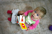 Potty training a toddler. Toddler sits on pot while reading a potty training manual. Model Release Available