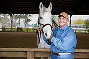 A senior man with white horse