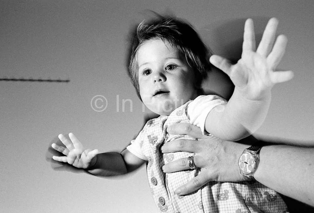 """Flight to Portugal."" An eleven month-old child stands on a restaurant  table and is held by her mother whilst holidaying on the Algarve, southern Portugal. Caught with side-lit flash and ambient Mediterranean evening light, her with arms and fingers are outstretched and the balancing infant girl who is learning to stand on her own before attempting to walk, pretends to fly in mid-air, relishing a sense of space and freedom. We see the experience of an adult encouraging a developing human being with the confidence to stand erect with back straight. This is from a documentary series of pictures about the first year of the photographer's first child Ella. Accompanied by personal reflections and references from various nursery rhymes, this work describes his wife Lynda's journey from expectant to actual motherhood and for Ella - from new-born to one year-old."