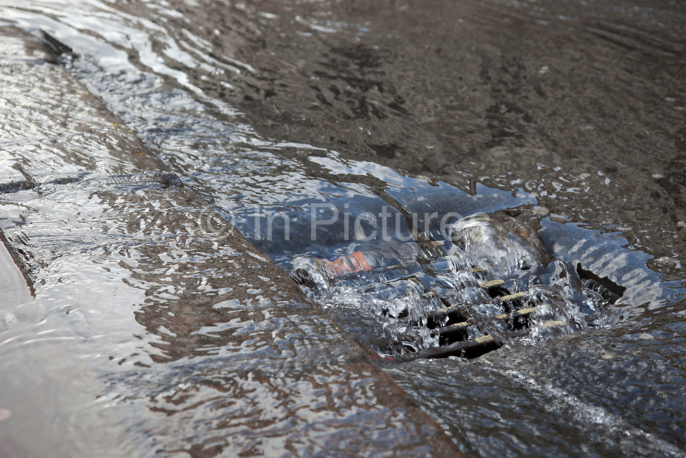 London, UK. Saturday 2nd March 2013. Burst water main causes flooding disruption in central London. Water flowing down a drain.
