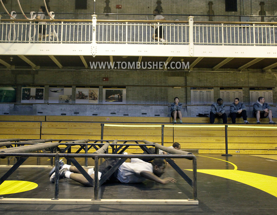 Cadets race through the low crawl, the first obstacle in the Indoor Obstacle Court Test, in Hayes Gym at the U.S. Military Academy at West Point on Feb. 9, 2010.