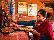 13 MARCH 2017 - PATAN, NEPAL: A woman sets out a small offering in a Hindu temple in Patan's Durbar Square.      PHOTO BY JACK KURTZ