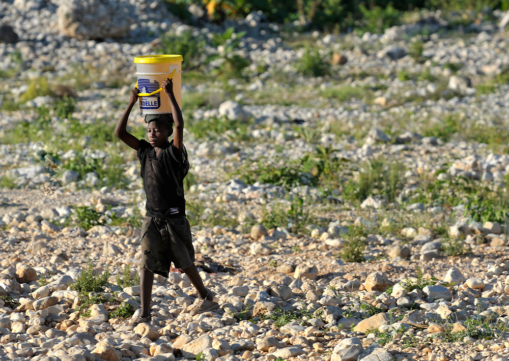 A boy carries a bucket of water on his head in Lastic le Roche, Haiti.