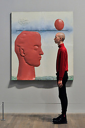 """© Licensed to London News Pictures. 17/10/2017. London, UK. A staff member views """"Head with a Balloon"""", 1965, at a preview of """"Not Everyone Will Be Taken Into The Future"""", the first UK exhibition by Russian artists Ilya and Emilia Kabakov.  The exhibition coincides with the 100th anniversary of the 1917 Russian Revolution and shows the couple's large scale installations and conceptual art.  Held at Tate Modern, the show runs 18 October to 28 January 2018. Photo credit : Stephen Chung/LNP"""