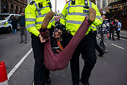 Police officers arrest protesters on Whitehall on 16th October 2019 in England, United Kingdom.  Extinction Rebellion climate activists sit down in the road despite the police imposing a section 14 of the Public Order Act 1986  in effect banning all protest by the group in London.