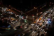 Dhaka, Bangladesh - November 1, 2017: Pedestrians wait to cross the street filled with heavy traffic at night in Dhaka.
