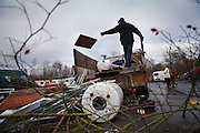 A scrap metal collector is classifying the metals. // France is the land of destination of many Roma people in their diaspora across Europe, who live camped in many settlements at the outskirts of cities. In 2013, the French Government has expelled thousands of Gypsies from the East as in 2010, 2011 and 2012, this time without any financial aids. Many Roma live afraid to be expelled but they remain in the French country with the hope of receiving some kind of aid. Outskirts of Lille, France. December 2013.