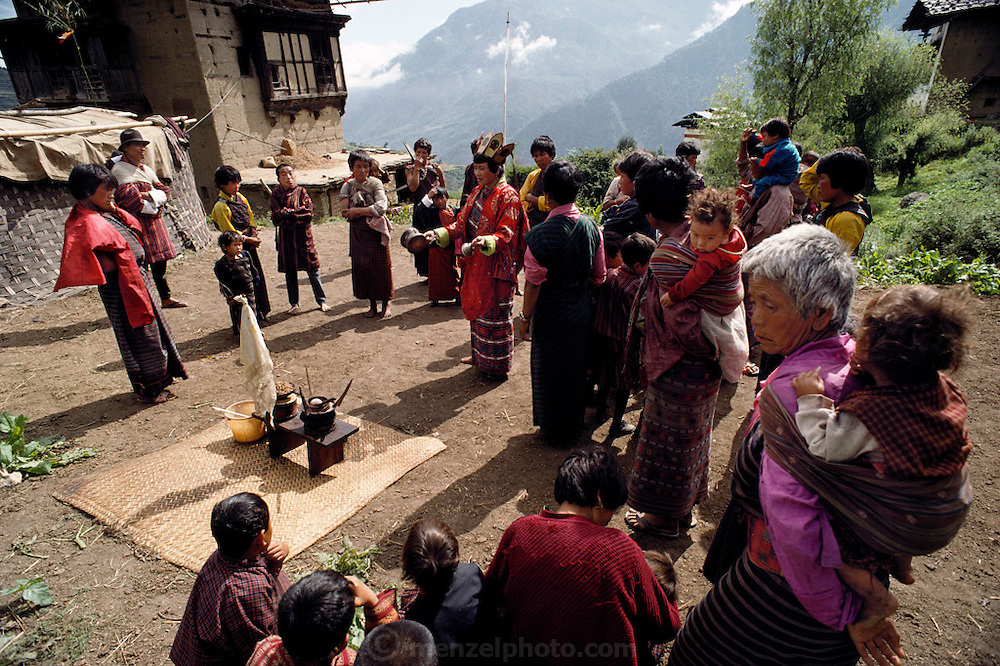 Outside the Shingkhey Buddhist Temple, a two-day ceremony is held to bless the village. To a continuous background of chanting, the monks fill the valley with long, slow, deep notes from their horns. Bhutan. From Peter Menzel's Material World Project.