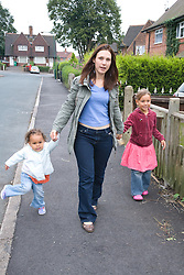 Mother walking with her young daughters in the street,