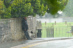 © Licensed to London News Pictures. 16/06/2020. Builth Wells, Powys, Wales, UK. A man with a dog takes shelters under some bushes during a thunderstorm in Builth Wells, Powys, UK. Thunderstorms and heavy rain hit Powys, Wales, UK. Photo credit: Graham M. Lawrence/LNP