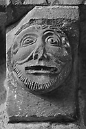 The Stone Bestiary - Black and white photo art print of Norman Romanesque exterior corbel no 40 - sculpture of a mans head.  The Norman Romanesque Church of St Mary and St David, Kilpeck Herefordshire, England. Built around 1140 .<br /> <br /> Visit our LANDSCAPE PHOTO ART PRINT COLLECTIONS for more wall art photos to browse https://funkystock.photoshelter.com/gallery-collection/Places-Landscape-Photo-art-Prints-by-Photographer-Paul-Williams/C00001WetsxVxNTo