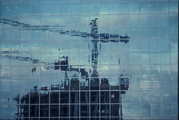 Stock photo of the reflection of construction cranes in a downtown building's windows