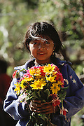 Young girl with bouquet of flowers in the cemetery on the Day of the Dead, in Todos Santos de Cuchumatan, Guatemala.